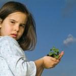 Girl holding plant — Stock Photo #1341138