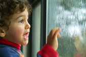 Little boy watching the rain — Stock Photo