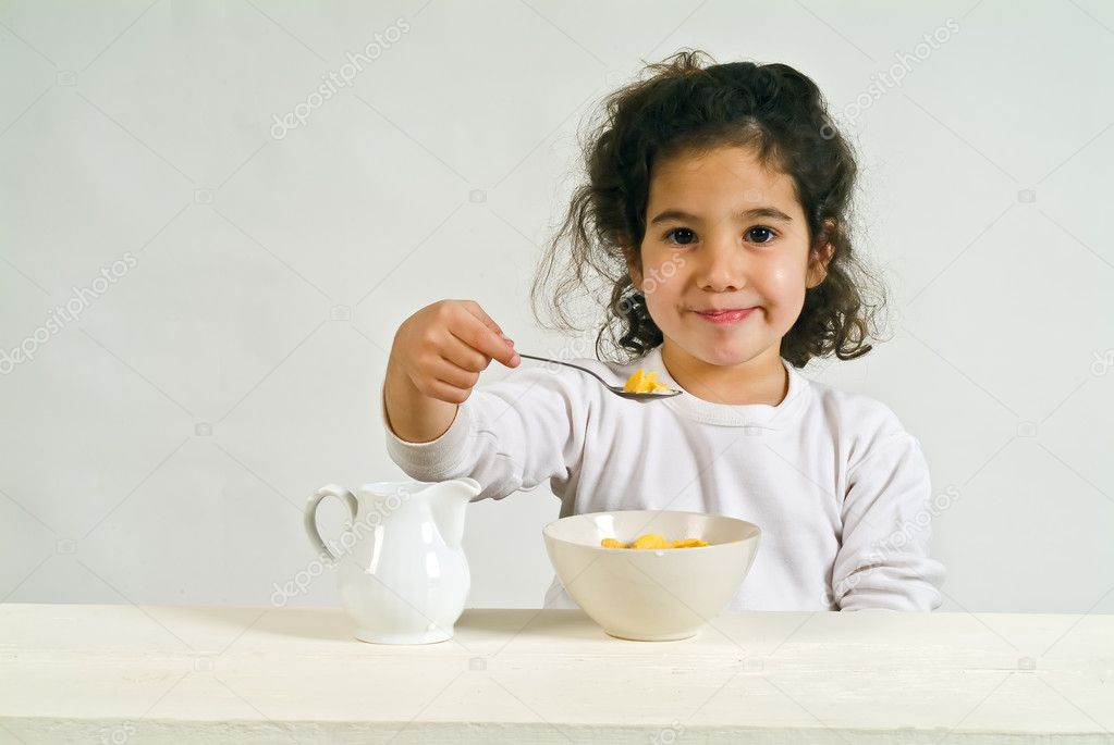 Little girl holding a spoon with cereals — Stock Photo #1340884