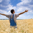 Stock Photo: Farmer in wheat field with arms spread out