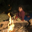 Boy at campfire - Stock Photo