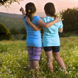 Two girls flowers field at sunset — Stock Photo