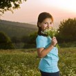 Girl holding flowers in field at sunset — Stock Photo
