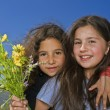 Royalty-Free Stock Photo: Two girls and yellow flowers