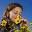 Stock Photo: Young girl smelling flowers