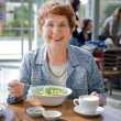 Senior women having salad and coffee - Stock Photo