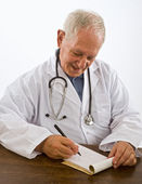 Doctor writing a prescription — Stock Photo