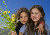 Two girls and yellow flowers — Stock Photo