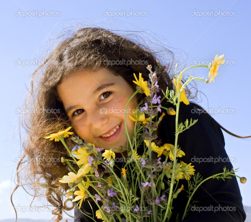 Little girl smiling holding wild flowers  Stock Photo #1413591