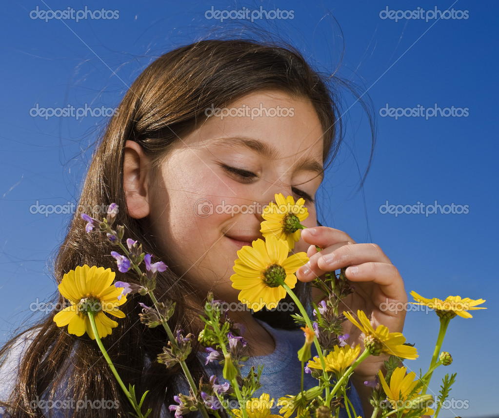Young girl smelling yellow wild flowers  Stock Photo #1413695