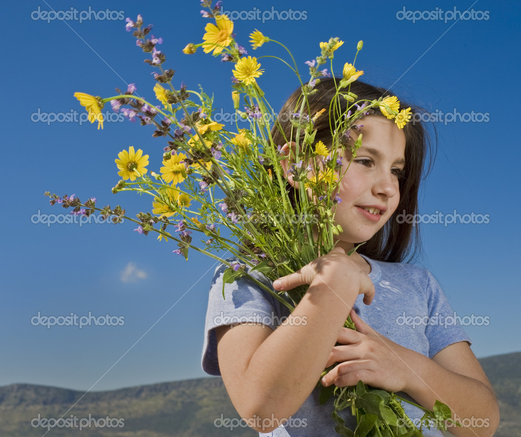 Young girl holding wild yellow flowers — Foto de Stock   #1413710