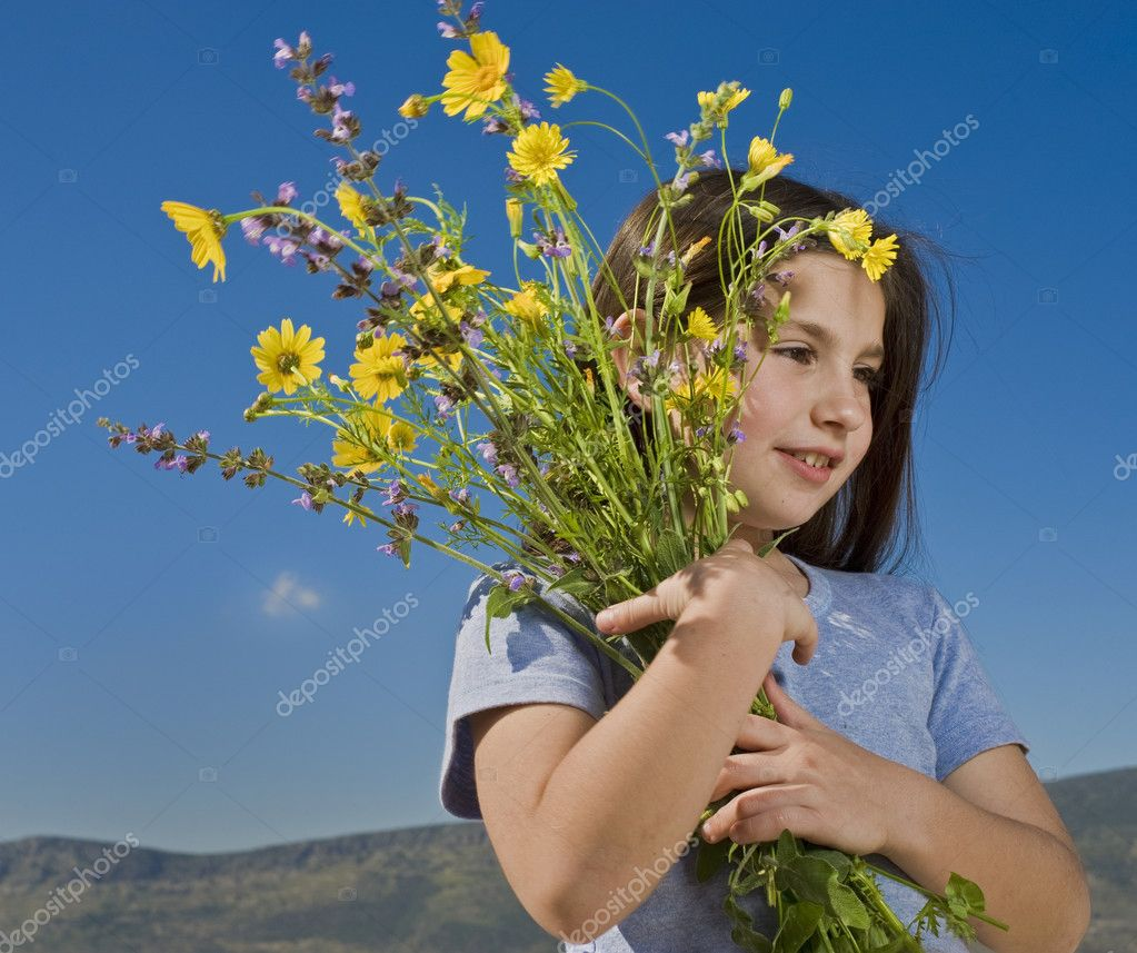 Young girl holding wild yellow flowers — Stock Photo #1413710