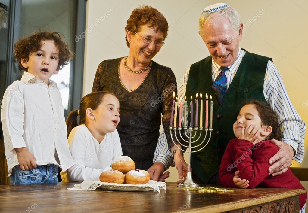 Grandperents and grandchildren lightening Hanukkiyah together — Stock Photo #1414837