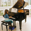 Little girl playing the piano - Stock Photo