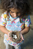 Little girl holding nest with eggs — Stock Photo