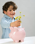 Boy piggy bank flowers — Stock Photo