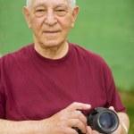 Senior man with digital camera — Stock Photo