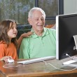 Grandfather and granddaughter with computer — Stock Photo