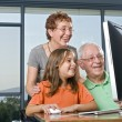 Grandparents and granddaughter with computer — Stock Photo