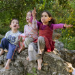Three kids singing outdoors - Stock Photo