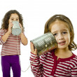 Two girls talking on a tin phone - Stock Photo