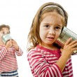 Two kids talking on a tin phone -  