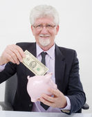 Senior businessman and piggybank — Stock Photo