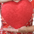 Woman holds a heart opposite the bust — Stock Photo