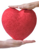 Red heart in male and female hands — Stock Photo