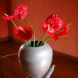 Stock Photo: Red flowers on glass table