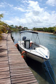 Motorboat by wooden pier — Stock Photo