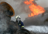 A fireman estinguishing fire of tyres — Stock Photo