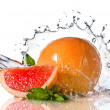 Water splash on grapefruit with mint i — Stock Photo