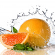 Water splash on orange with mint — Stock Photo