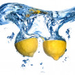 Fresh lemon dropped into water - Stock Photo