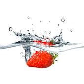 Fresh strawberry dropped into water — Stock Photo