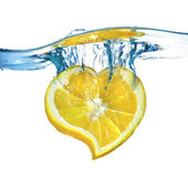Heart from the lemon dropped into water — Stock Photo