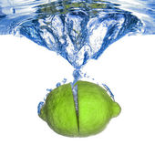 Fresh lime dropped into water — Stockfoto