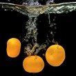 Fresh tangerines dropped into water — Stock Photo