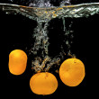 Stock Photo: Fresh tangerines dropped into water
