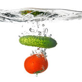 Tomato and cucumber dropped into water — Stock Photo