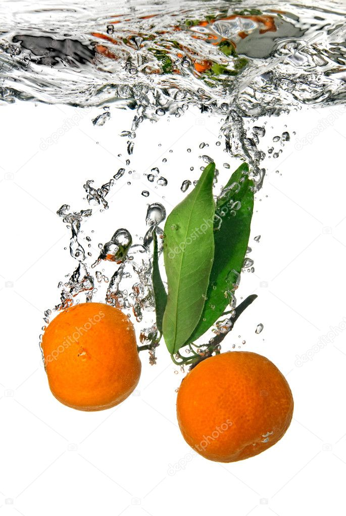 Tangerine dropped into water with bubbles on white — Stock Photo #2621964