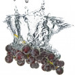 Blue grape dropped into water - Stock Photo