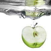 Fresh water splash on green apple — Stock Photo