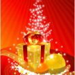 Golden gift-box in front of the xmas tre — Stock Photo