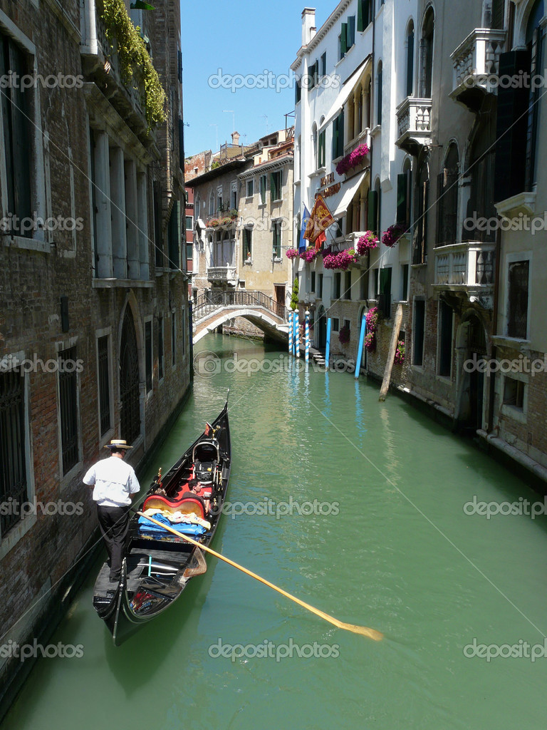 Gondolier paddling his gondola through a small channel in Venice, Italy. — Stock Photo #1551188