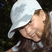 The smiling girl in a cap — Stock fotografie