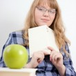 The girl with the book looks at an apple — Stock Photo