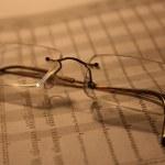 Eyeglasses on finance sheet — Stock Photo