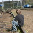 Boy sitting on rail track - Stock Photo